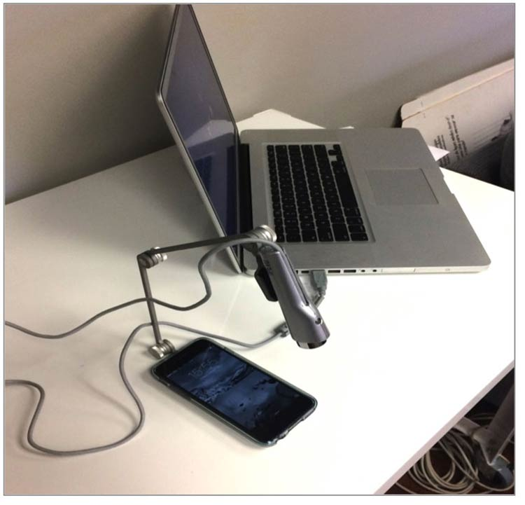 Mobile usability testing set up — a laptop and a camera above a mobile phone on a desk