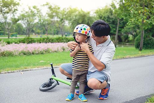 Parent putting bike helmet on child.