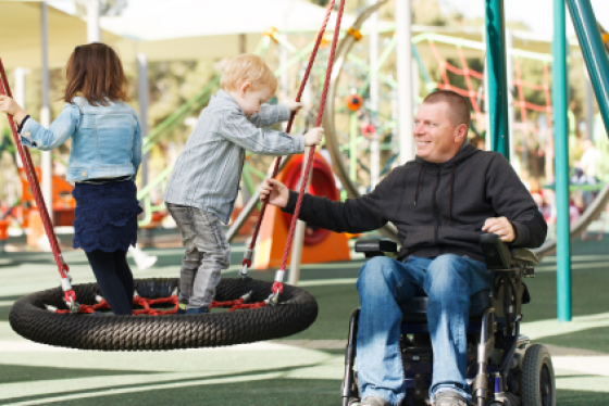 Man in wheelchair pushing children on tire swing