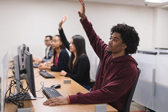 Four students sit at computer desks in class, two raise their hands.