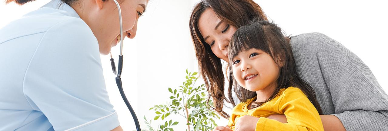 Health care provider using stethoscope on child.