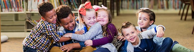 Six young children sit in a line on the floor of a library and hug each other.
