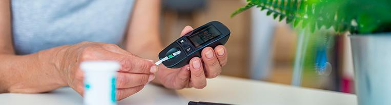 A woman checks her blood sugar with a blood glucose meter.