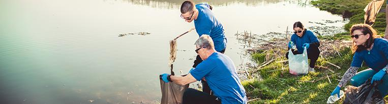 Volunteers wearing gloves and holding trash bags clean up litter at a lake.