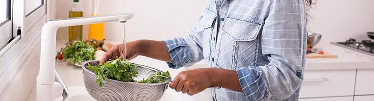 A woman rinses parsley in a colander at her kitchen sink.