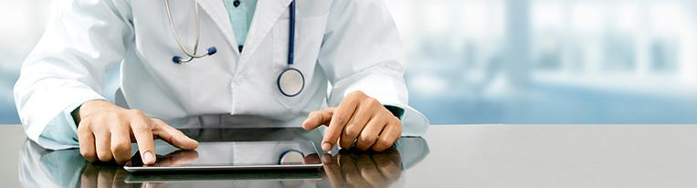 A health care provider sits at a desk and uses a tablet.