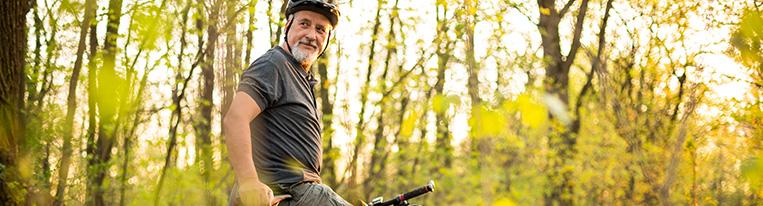 A man wearing a bicycle helmet and biking on a wooded trail pauses to look over his shoulder.