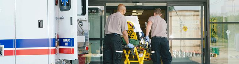 Two paramedics wheel a person on a stretcher into a hospital.