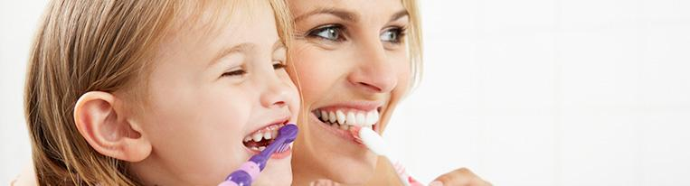 A woman and her young daughter smile while brushing their teeth over a sink.