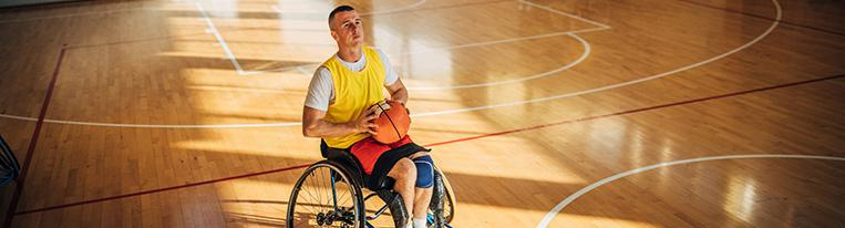 A man in a wheelchair on an indoor basketball court prepares to shoot a basket.