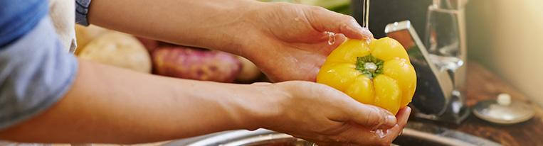 A person washes a yellow bell pepper under a kitchen faucet.