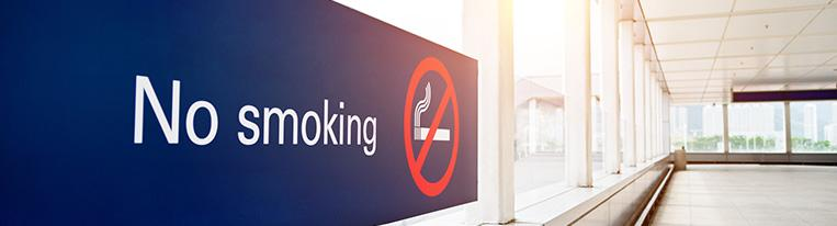 A no smoking sign hangs in a window-lined hallway.
