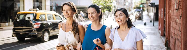 Three women holding shopping bags walk along a city street together.