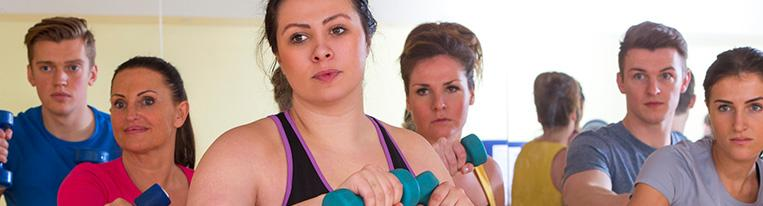 Six people use small weights in an exercise class.