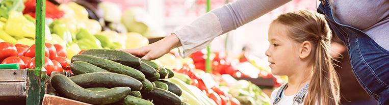 A pregnant mother and her young daughter look at cucumbers in the produce section of a supermarket.