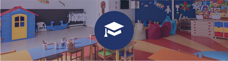 A mortarboard icon overlays a colorful preschool classroom filled with artwork and art supplies, tables and chairs, and riding toys.