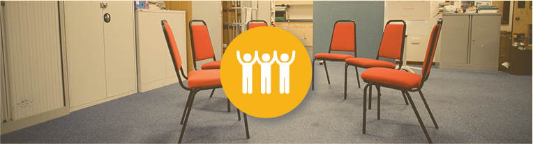 An icon of 3 people overlays a circle of red chairs in a community center.