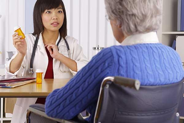 A doctor and elderly patient sitting across from one another and talking
