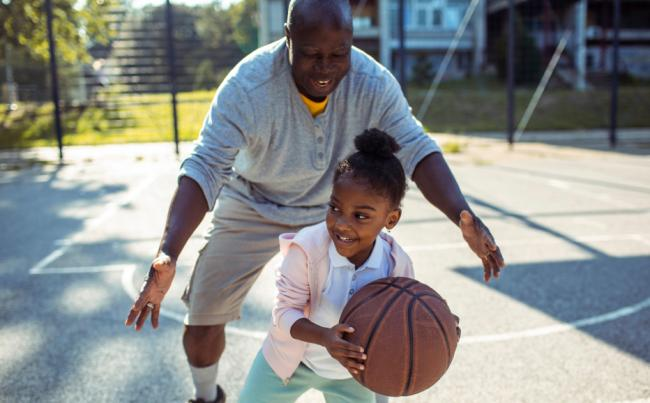 A little girl and her dad play basketball on an outdoor court.