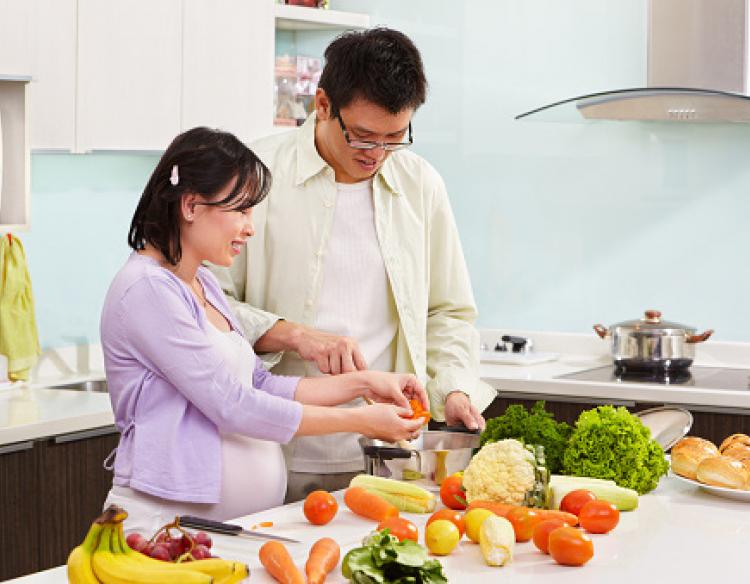 Man and pregnant woman preparing healthy produce for a meal