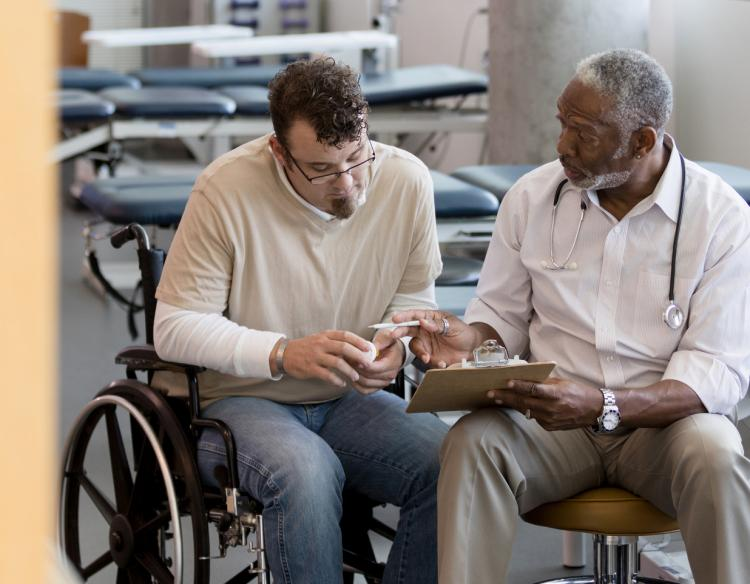 Man in wheelchair speaking with his provider