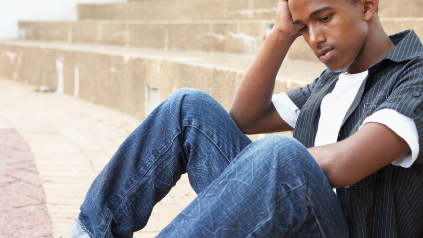 Teenage boy sitting on the ground with his head in his hand
