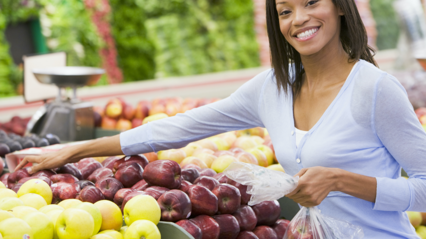 Smiling woman shopping for fruits and vegetables