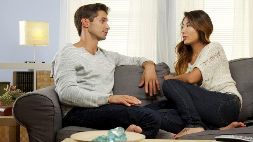 A man and a woman sitting on a couch and talking